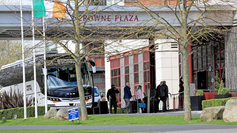 DUBLIN, IRELAND - MARCH 29: Airline passengers leave the bus to enter the Crowne Plaza hotel to begin their period of quarantine on March 29, 2021 in Dublin, Ireland. Last week, Ireland started requiring travelers from 33 high-risk countries to be shuttled to a mandatory 12-day hotel quarantine. Over the weekend, three quarantined travelers absconded from their hotel, forcing authorities to track them down. (Photo by Donall Farmer/Getty Images)