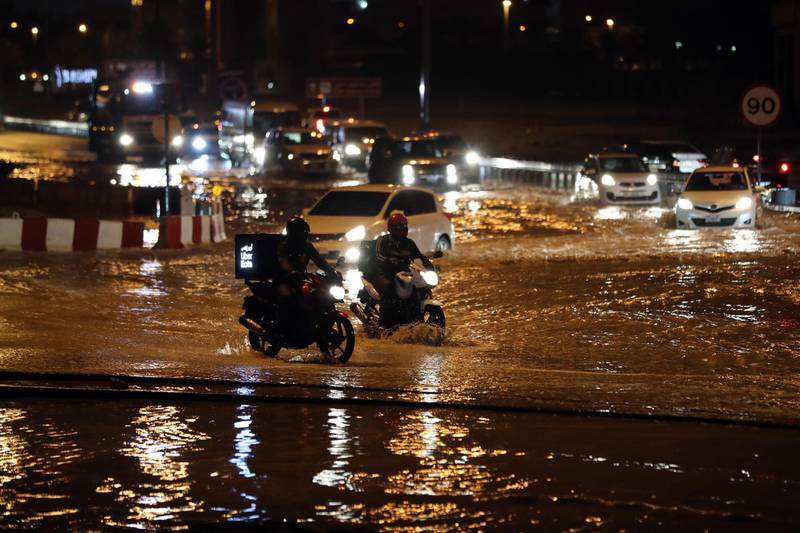 Dubai, United Arab Emirates - Reporter: N/A: Weather. Cars and motorbikes try to get through flooding on a roundabout near studio city. Saturday, March 21st, 2020. Dubai. Chris Whiteoak / The National