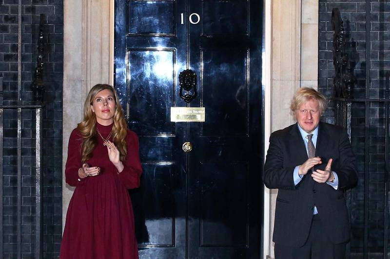 LONDON, ENGLAND - FEBRUARY 03: United Kingdom prime minister Boris Johnson and his fiancee Carrie Symonds take part in a doorstep clap in memory of Captain Sir Tom Moore outside 10 Downing Street on February 03, 2021 in London, England. WWII veteran, Sir Tom had raised nearly £33 million for NHS charities ahead of his 100th birthday last year by walking laps of his garden in Marston Moretaine, Bedfordshire. He was admitted to Bedford Hospital this weekend after testing positive for covid-19 and died on 2nd February with his family present. (Photo by Hollie Adams/Getty Images)