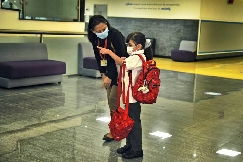 Member of Al-Mizhar American Academy for Girls assists a student wearing protective masks as they return to school after months on Sunday, Aug. 30, 2020, in Dubai, UAE. (Photos by Shruti Jain - The National)