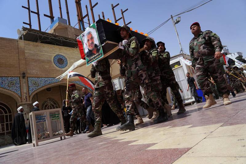 Members of Iraq's Shiite Muslim Hashed al-Shaabi (Popular Mobilisation units) paramilitary force carry the coffin of their comrade Kazem Mohsen, known by his nom de guerre Abu Ali al-Dabi, during his funeral procession in the central shrine city of Najaf south of the Iraqi capital Baghdad on August 26, 2019.  The Iraqi fighter was killed in a drone attack late yesterday near the western border with Syria, in the latest in a string of suspicious explosions and drone sightings at Hashed bases across Iraq but the first time that the group specifically blamed Israel.  / AFP / Hashed al-Shaabi Media / Haidar HAMDANI