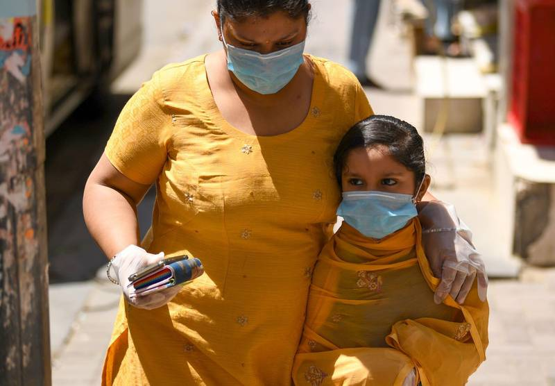 A mother and daughter, wearing protective gloves and face masks, walk together in the Emirate city of Dubai on March 31, 2020, after the country imposed a sweeping crackdown, closing its borders and halting passenger flight among others measures to contain the virus. The UAE, which takes in seven emirates including Dubai, has reported 611 coronavirus cases along with five deaths.  / AFP / KARIM SAHIB