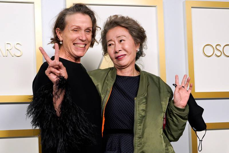 """Frances McDormand, winner of the award for best actress in a leading role for """"Nomadland,"""" and Yuh-Jung Youn, winner of the award for best actress in a supporting role for """"Minari,"""" pose in the press room at the Oscars, in Los Angeles, California, U.S., April 25, 2021. Chris Pizzello/Pool via REUTERS"""
