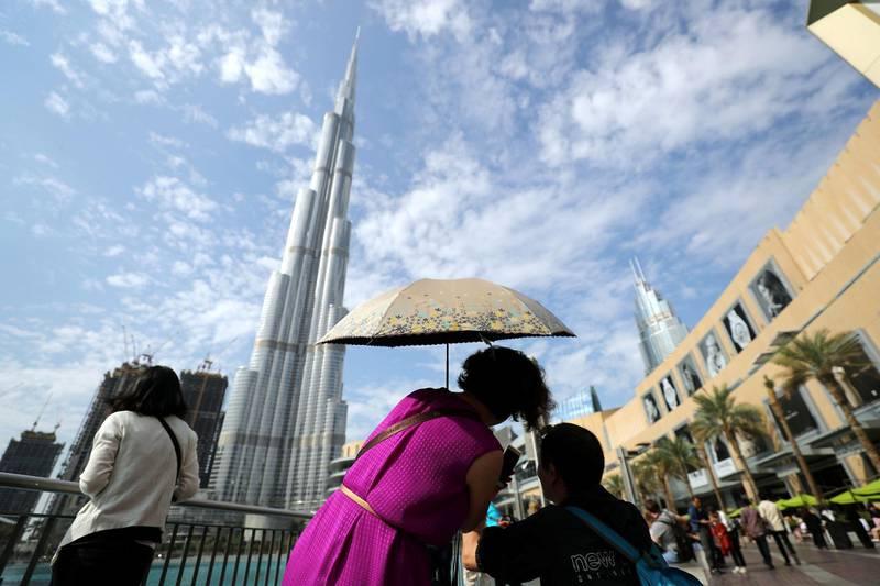 Dubai, United Arab Emirates - November 25, 2019: Standalone. Visitors to Dubai mall take pictures of the Burj Khalifa while covering up from the sun on a beautiful day in Dubai. Monday, November 25th, 2019 at Dubai Mall, Dubai. Chris Whiteoak / The National