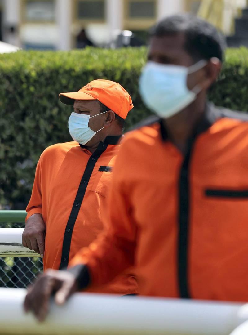 Dubai, United Arab Emirates - Reporter: Amith Passela: Two grooms wear face masks on race day at Jebel Ali. Friday, March 20th, 2020. Jebel Ali Racecourse, Dubai. Chris Whiteoak / The National