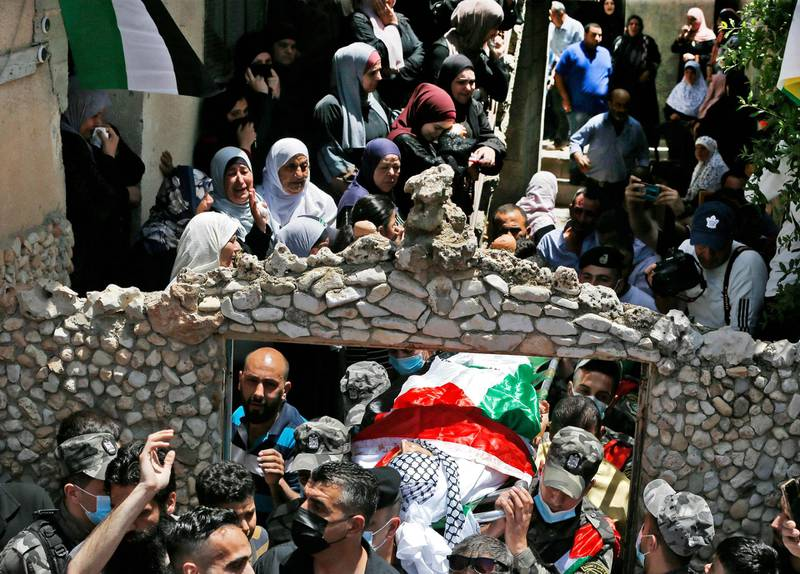 """Relatives of Ahmed Daraghmeh, a member of Palestinian intelligence services who was killed by Israeli forces the previous day at the Zaatara (Tapuach) junction south of Nablus in the occupied West Bank, look on as his body passes below during a funerary procession in the town of al-Lubban al-Sharqiya near Nablus on May 12, 2021. Daraghmeh, 30, was killed and another Palestinian wounded by Israeli army gunfire in the north of the occupied West Bank as violence soared between Israel and the Palestinian territories. Both were shot at an Israeli army checkpoint near Nablus. The Israeli army earlier reported an """"attempted drive-by shooting at Tapuah Junction"""" near Nablus. / AFP / ABBAS MOMANI"""