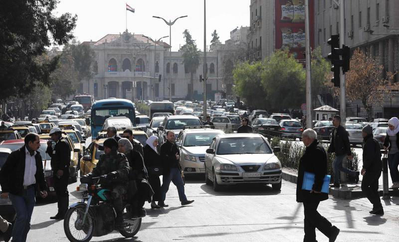 Syrians walk past the traffic in the streets of Hijaz in Damascus on January 21, 2019.   Israel struck what it said were Iranian targets in Damascus early today in response to missile fire it blamed on Iran, sparking concerns of an escalation after a monitor reported 11 fighters killed. / AFP / LOUAI BESHARA