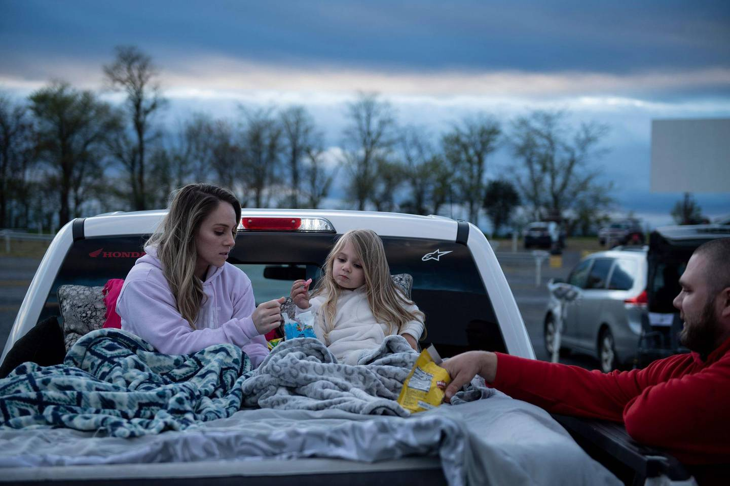 Summer Edwards, Kimberlyn Edwards, and Chance Edwards eat snacks while waiting for the movie to start at the Family Drive-In Theatre during its opening night amid novel coronavirus restrictions on May 1, 2020, in Stephens City, Virginia. The theatre managment implemented special coronavirus policies to insure everyone safety. Virginia Governor Ralph Northam had ordered the closing of nonessential businesses through May 8, he is scheduled to present new guidelines on May 4. / AFP / Brendan Smialowski