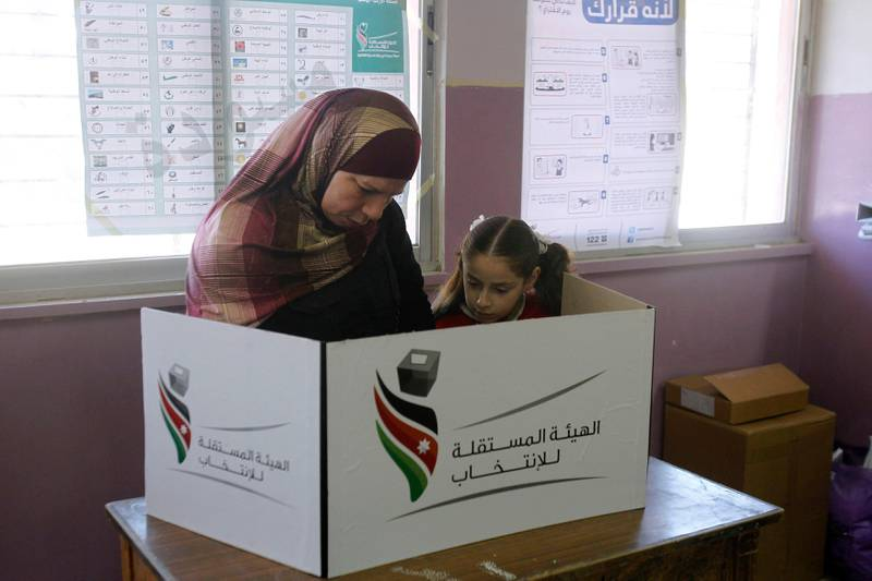 A girl watches as her mother votes at a polling station in Amman January 23, 2013. Polling stations opened on Wednesday in Jordanian elections boycotted by the Muslim Brotherhood, which says the electoral system is rigged in favour of tribal areas and against the large urban centres. Eyewitnesses reported queues of about a dozen people apiece at several polling stations across the kingdom just before the polls opened at 7 a.m. (0400 GMT).   REUTERS/Ali Jarekji  (JORDAN - Tags: POLITICS ELECTIONS) *** Local Caption ***  AMM02_JORDAN-ELECTI_0123_11.JPG