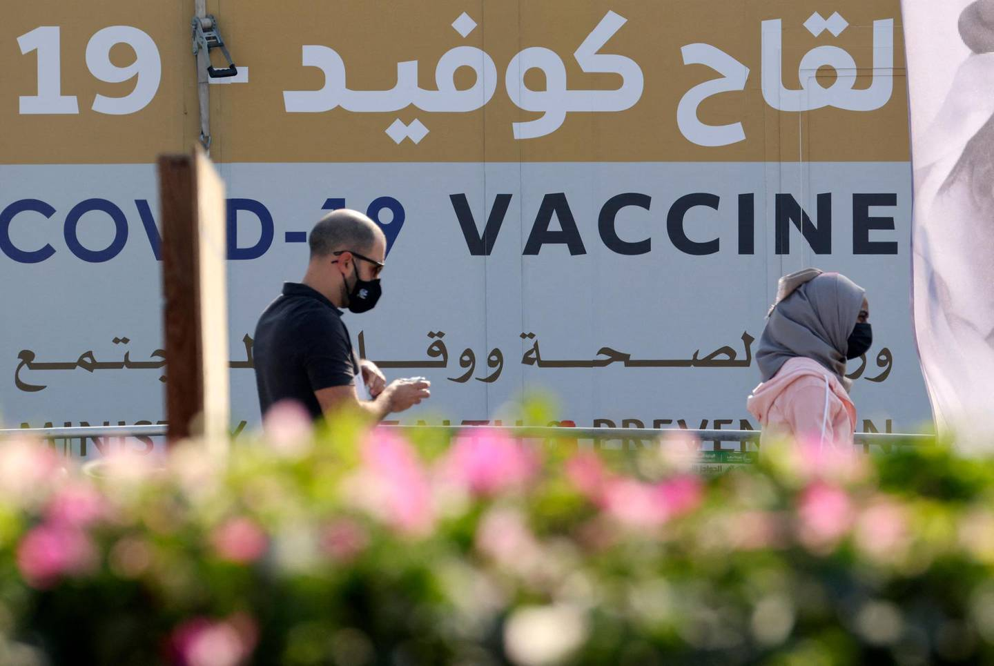 A man and a woman walk past a huge health ministry COVID-19 vaccines announcement outside a medical centre in Dubai on February 16, 2021, as the Gulf emirates goes ahead its vaccination effort. The UAE, home to a population of around 10 million, has administered some 4.6 million doses of vaccine, making it the second-fastest per capita delivery in the world, after Israel. / AFP / Karim SAHIB