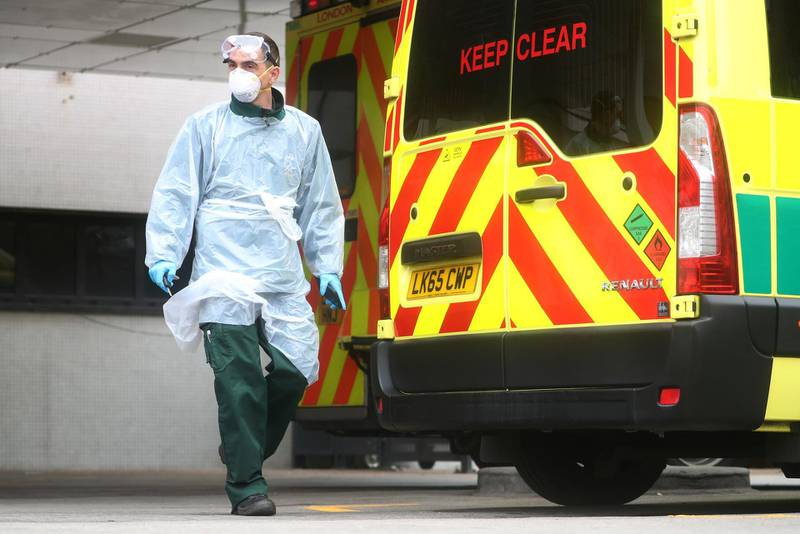 A paramedic wearing a protective face mask and gloves is seen at the back of an ambulance outside St Thomas' hospital, as the spread of the coronavirus disease (COVID-19) continues, London, Britain, April 1, 2020. REUTERS/Hannah McKay