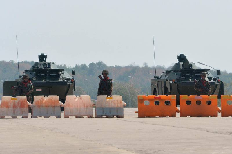 Soldiers stand guard on a blockaded road to Myanmar's parliament in Naypyidaw on February 1, 2021, after the military detained the country's de facto leader Aung San Suu Kyi and the country's president in a coup. (Photo by STR / AFP)