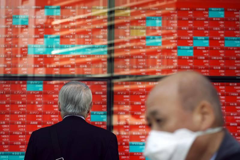 A man wearing a mask against the spread of the coronavirus looks at an electronic stock board showing Japan's Nikkei 225 index at a securities firm in Tokyo Monday, Nov. 16, 2020. Shares started out the week on a strong footing after the Standard & Poors 500 hit a fresh high on Friday, with strong data from Japan and China fueling optimism over economic recoveries even as coronavirus caseloads surpass earlier records. (AP Photo/Eugene Hoshiko)