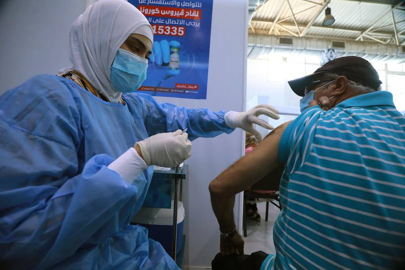 epa09229228 A nurse administers a dose of the COVID-19 vaccine to an elderly man at a mass immunization venue inside Cairo's International Exhibition Center, in Cairo, Egypt, 26 May 2021.  EPA/KHALED ELFIQI