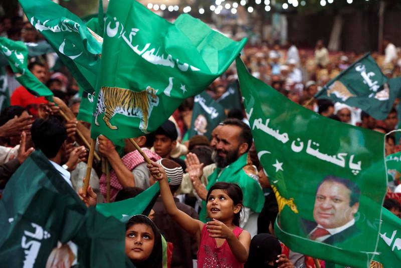 A child supporter of Shahbaz Sharif, brother of ex-prime minister Nawaz Sharif, and leader of Pakistan Muslim League - Nawaz (PML-N) waves party flags with others to welcome him during a campaign rally ahead of general elections in the Lyari neighborhood in Karachi, Pakistan June 26, 2018. REUTERS/Akhtar Soomro