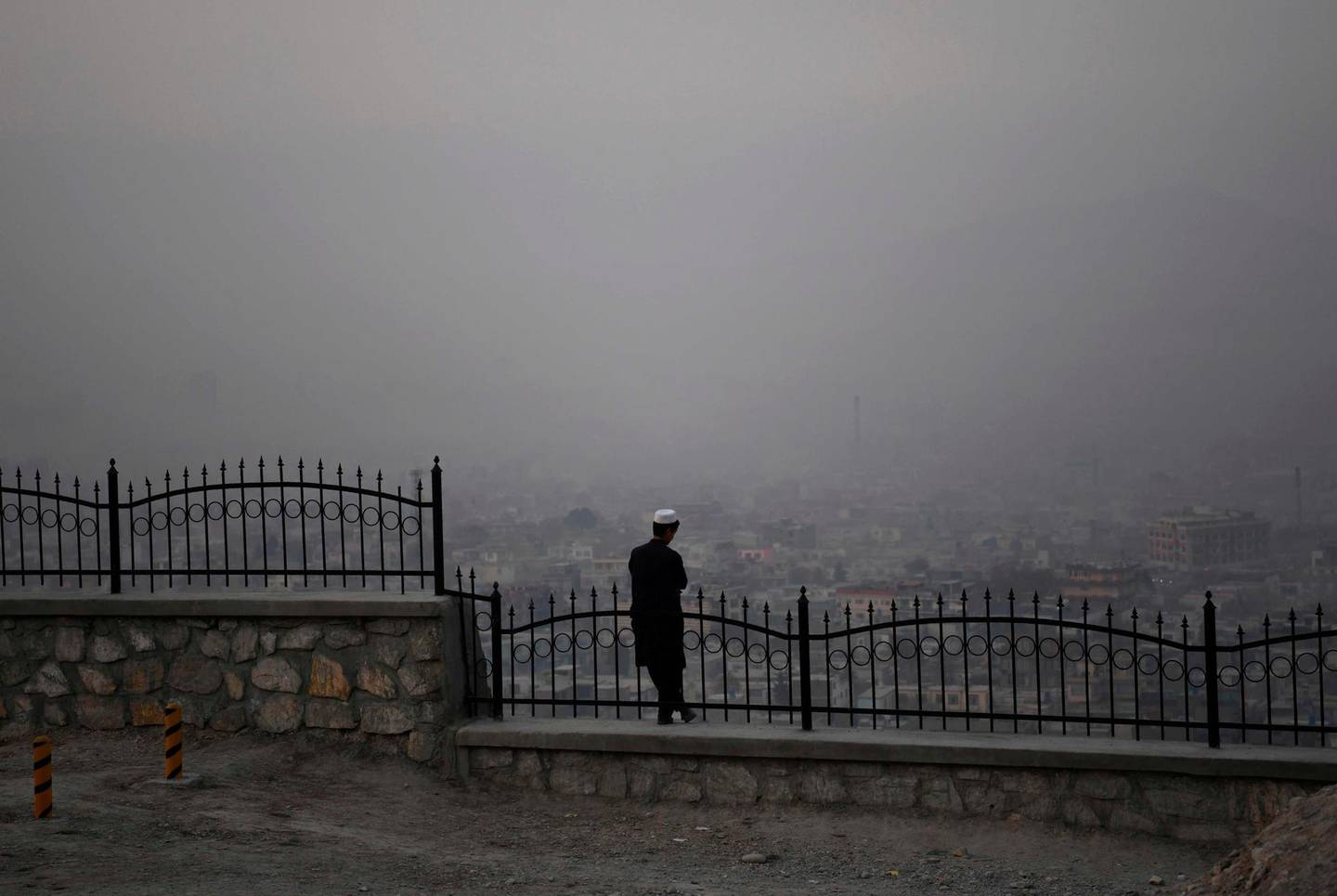 A youth looks down the city from a hilltop amid smog and foggy conditions on a cold afternoon in Kabul on December 29, 2019.  / AFP / FARSHAD USYAN
