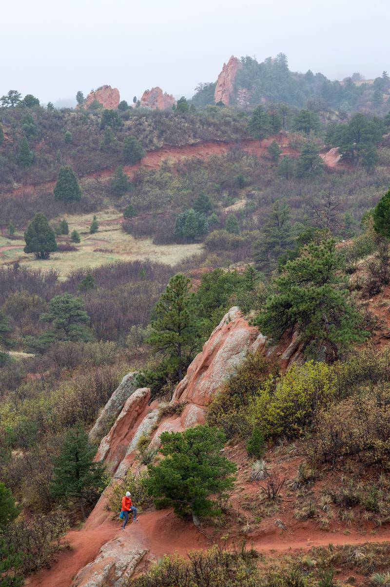 A visitor hikes the quiet Quarry Pass Trail in Red Rocks Canyon Open Space, Monday, May 10, 2021, as a drizzle soaks the Colorado Springs, Colo., park. Rain and snow is expected in the Pikes Peak Region until Wednesday. (Christian Murdock/The Gazette via AP)
