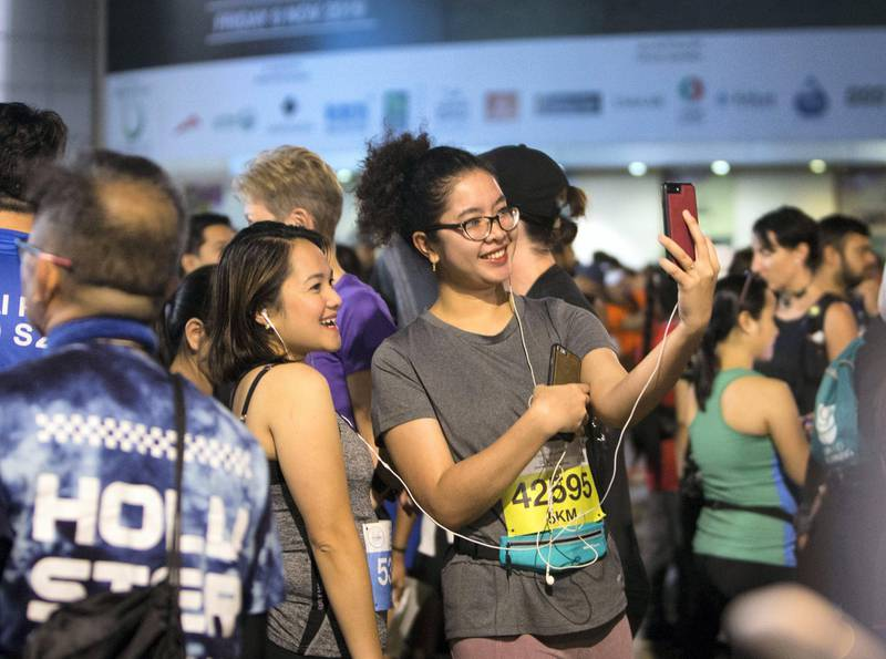 Dubai, United Arab Emirates - Participants before the run doing selfie  at the Dubai 30x30 Run at Sheikh Zayed Road.  Leslie Pableo for The National