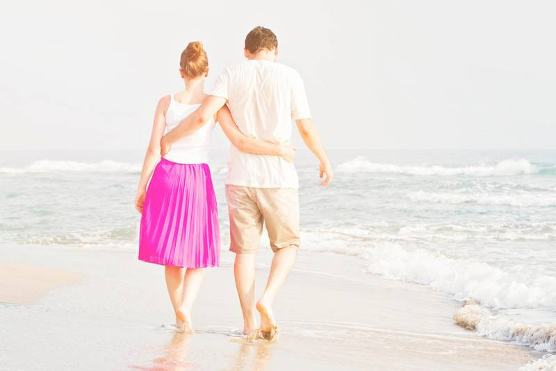 Young adult male and female holding hands on beach at sunset. Getty Images