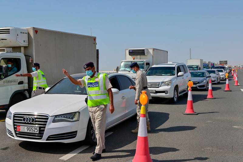 Emirati security forces man a checkpoint at the entrance of Abu Dhabi, on the highway linking Dubai to the capital, on June 2, 2020, after authorities cordoned off the city for a week to rein in the novel coronavirus.  / AFP / Giuseppe CACACE
