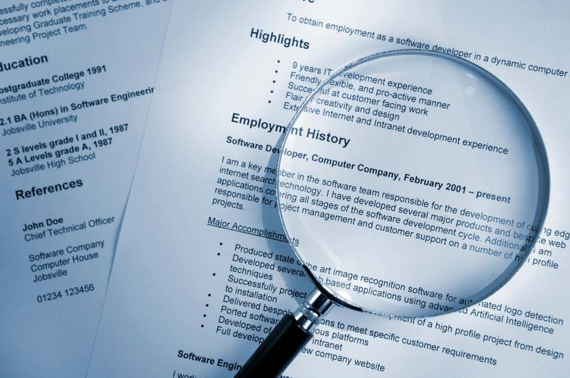 A blue tinted image of a magnifying glass lying on top of several sheets of a printout of resume documents. All information on the resume is fake. Getty Images