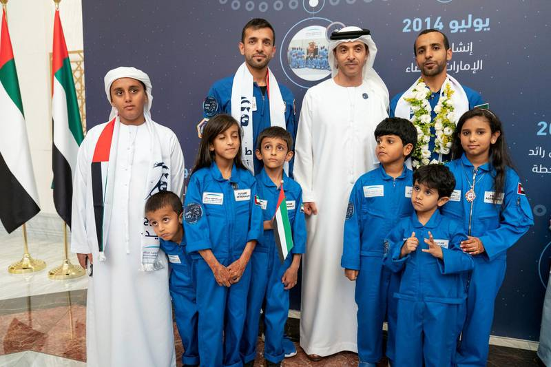 ABU DHABI, UNITED ARAB EMIRATES - October 12, 2019: HH Sheikh Hazza bin Zayed Al Nahyan, Vice Chairman of the Abu Dhabi Executive Council (back 2nd R), stands for a photograph with Hazza Ali Al Mansoori, the first UAE Astronaut to be deployed on a space mission to the International Space Station (ISS) (back R) and Sultan Saif Al Neyadi, a member of the International Space Station (ISS) mission back-up team (back 3rd R), during a home-coming reception, at the Presidential Airport.   ( Hamad Al Mansoori for the Ministry of Presidential Affairs ) ---