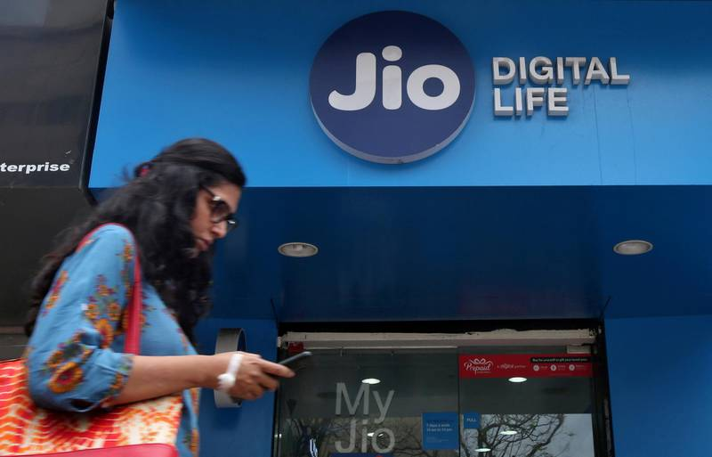 FILE PHOTO: A woman checks her mobile phone as she walks past a mobile store of Reliance Industries' Jio telecoms unit, in Mumbai, India, July 11, 2017. REUTERS/Shailesh Andrade/File Photo