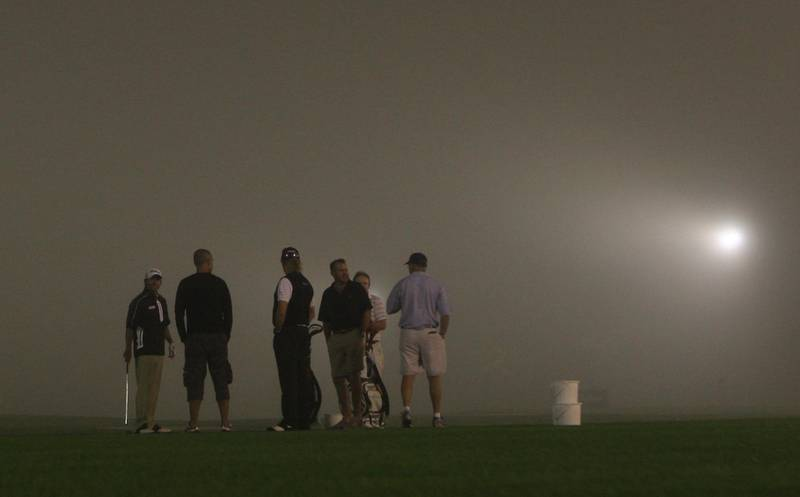 Dubai, UAE, Feb 10, 2011, Dubai Desert Classic Day 1- (center back to camera ) Miguel Angel Jimenez and other golfers on the fog covered range at the Dubai Desert Classic.  Mike Young / The National