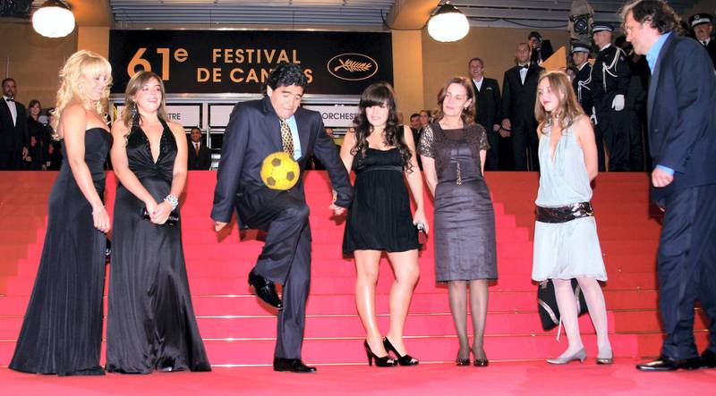 """Former Argentinian football player Diego Maradona (C) dribbles with a ball surrounded by (from L) his wife of Claudia, daughters Dalma and Giannina, Serbian producer Maja Kusturica, Dunja Kusturica and Serbian director Emir Kusturica as he arrives to attend the screening of the documentary film 'Maradona by Kusturica' at the 61st Cannes International Film Festival on May 20, 2008 in Cannes, southern France. The May 14-25 festival winds up with the awards ceremony for the prestigious Palme d'Or, to be determined by a jury headed by Hollywood """"bad boy"""" Sean Penn.     AFP PHOTO / Valery Hache (Photo by Valery HACHE / AFP)"""