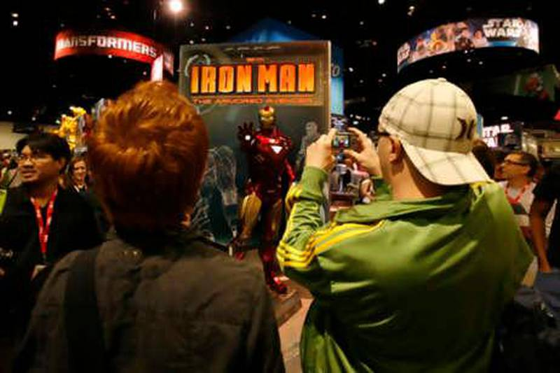 Attendees take photographs of a life size statue of Iron Man while on the convention floor during the opening night of the annual Comic Con in San Diego, California  July 21, 2010.  REUTERS/Mike Blake  (UNITED STATES - Tags: SOCIETY)