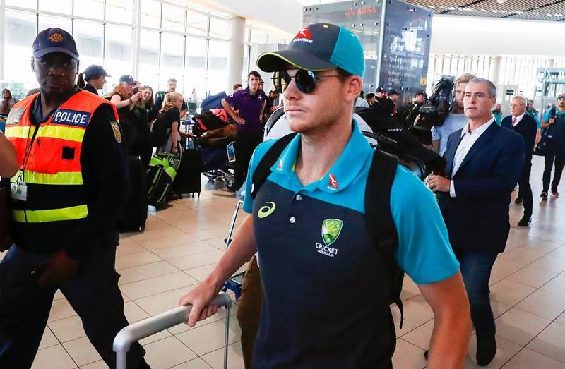epa06631768 Australian cricket captain Steve Smith (C) departs from Cape Town International airport, South Africa, 27 March 2018. Australia skipper Steve Smith has been suspended by the International Cricket Council (ICC) for his part in a ball tampering scandal during the third test against South Africa. Smith admitted some senior players were aware of the ball tampering attempt. Smith and David Warner stepped down as captain and vice-captain of the Australian team in consequence to the ball meddling scandal.  EPA/NIC BOTHMA