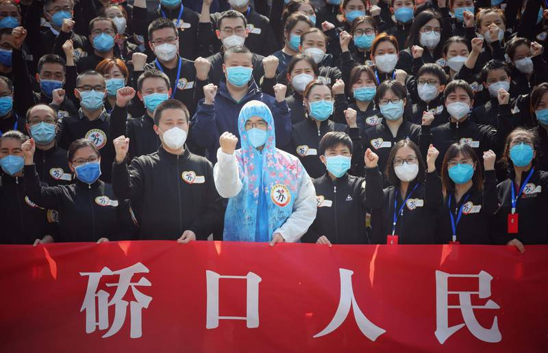TOPSHOT - Members of a medical assistance team from Jiangsu province chant slogans at a ceremony marking their departure after helping with the COVID-19 coronavirus recovery effort, in Wuhan, in China's central Hubei province on March 19, 2020. Medical teams from across China began leaving Wuhan this week after the number of new coronavirus infections dropped. China on March 19 reported no new domestic cases of the coronavirus for the first time since it started recording them in January, but recorded a spike in infections from abroad. - China OUT  / AFP / STR