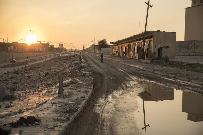 A person stands in a street next to damaged buildings in West Mosul, Iraq, on Thursday, Nov. 8, 2018. More than a year after the brutal fighting that liberated the city ended, and a devastating air campaign that mostly flattened it, much of Mosul lies in ruins. Few residents have returned and there is little commercial activity other than the destruction of devastated buildings and scavenging for metal. Photographer: Victor J. Blue/Bloomberg