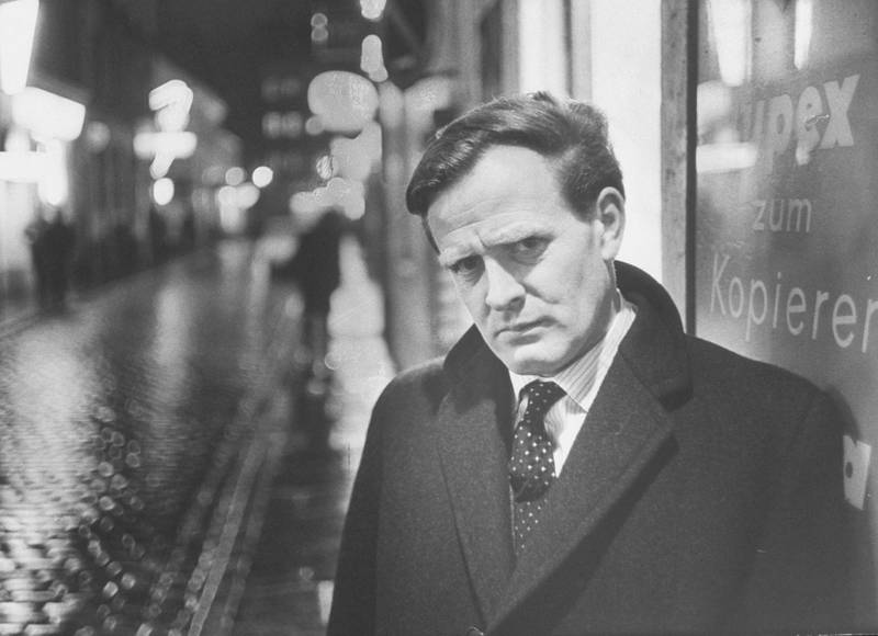 As photographic setting for picture story of British spy-thriller writer David Cornwell, shown on dark rainy street in Hamburg, looking suitably furtive in spy manner, 1964.  (Photo by Ralph Crane/The LIFE Picture Collection via Getty Images)