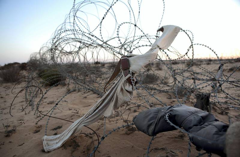 Items of clothing  from African asylum seekers are seen amongst the barbed wire fence along the border between Israel and Egypt on June 9 ,2012. Thousands of migrants  asylum seekers and refugees, primarily from Eritrea and Sudan, have traveled through Egypt and crossed the Sinai border into Israel. Many have lost their lives and have been tortured by Bedouin smugglers. (Photo by Heidi Levine/Sipa Press).//LEVINE_111010287/Credit:Heidi Levine/SIPA/1605172007 *** Local Caption *** 00756072