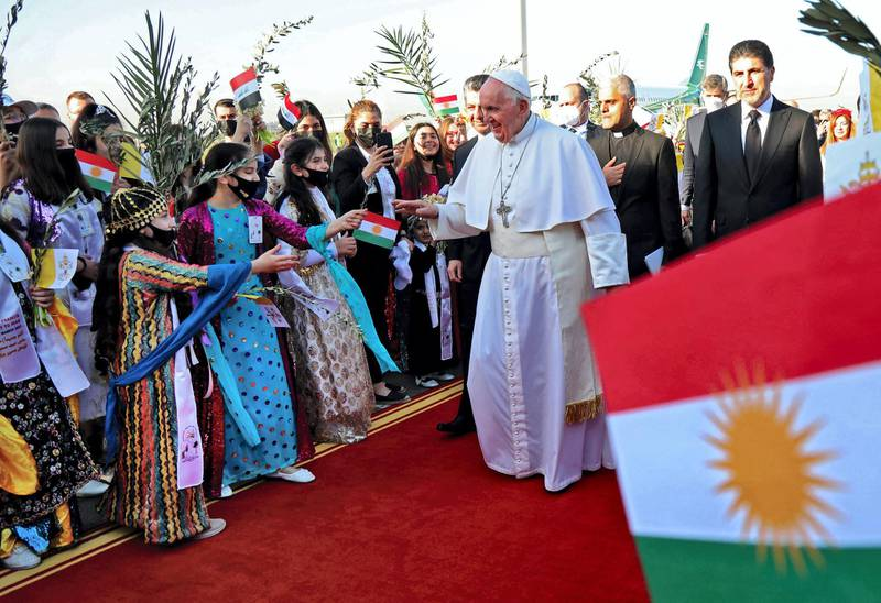 """Pope Francis greets Iraqis dressed in traditional outfits upon his arrival at Erbil airport on March 7, 2021, in the capital of the northern Iraqi Kurdish autonomous region. Pope Francis, on his historic Iraq tour, visits today Christian communities that endured the brutality of the Islamic State group until the jihadists' """"caliphate"""" was defeated three years ago. / AFP / Safin HAMED"""
