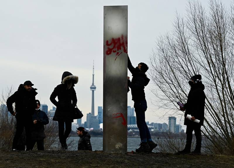A man tries to clean graffiti from the vandalized monolith as people look at a metallic monolith that appeared on the shorelines of Humber Bay Park during the COVID-19 pandemic in Toronto on Friday, Jan. 1, 2021. (Nathan Denette/The Canadian Press via AP)