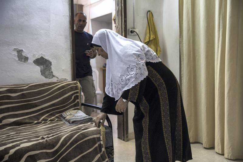 Mohamed Shamasneh watches his mother Fahima as she  fixes the blanket covering her sofa after she prayed in her tiny basement  home in the East Jerusalem neighborhood of Sheik Jarrah on August 11,2017.  When thehamasne family first moved into their home  in the 1960s, East Jerusalem was controlled by Jordan and their monthly rent was paid to  Jordanian authorities but since  Israel annexed East Jerusalem in 1967, the Shamasne family has paid their rent to Israel's general custodian in order to remain in the building. The family claims that their payments were suddenly rejected in 2009 , and they were informed that the property had been claimed by Israeli Jews whose ancestors had lived there decades previously.Although the family has spent years fighting to remain in the home , the Israeli high court has ruled that the family must evacuate the home before August 9. (Photo by Heidi Levine for The National).