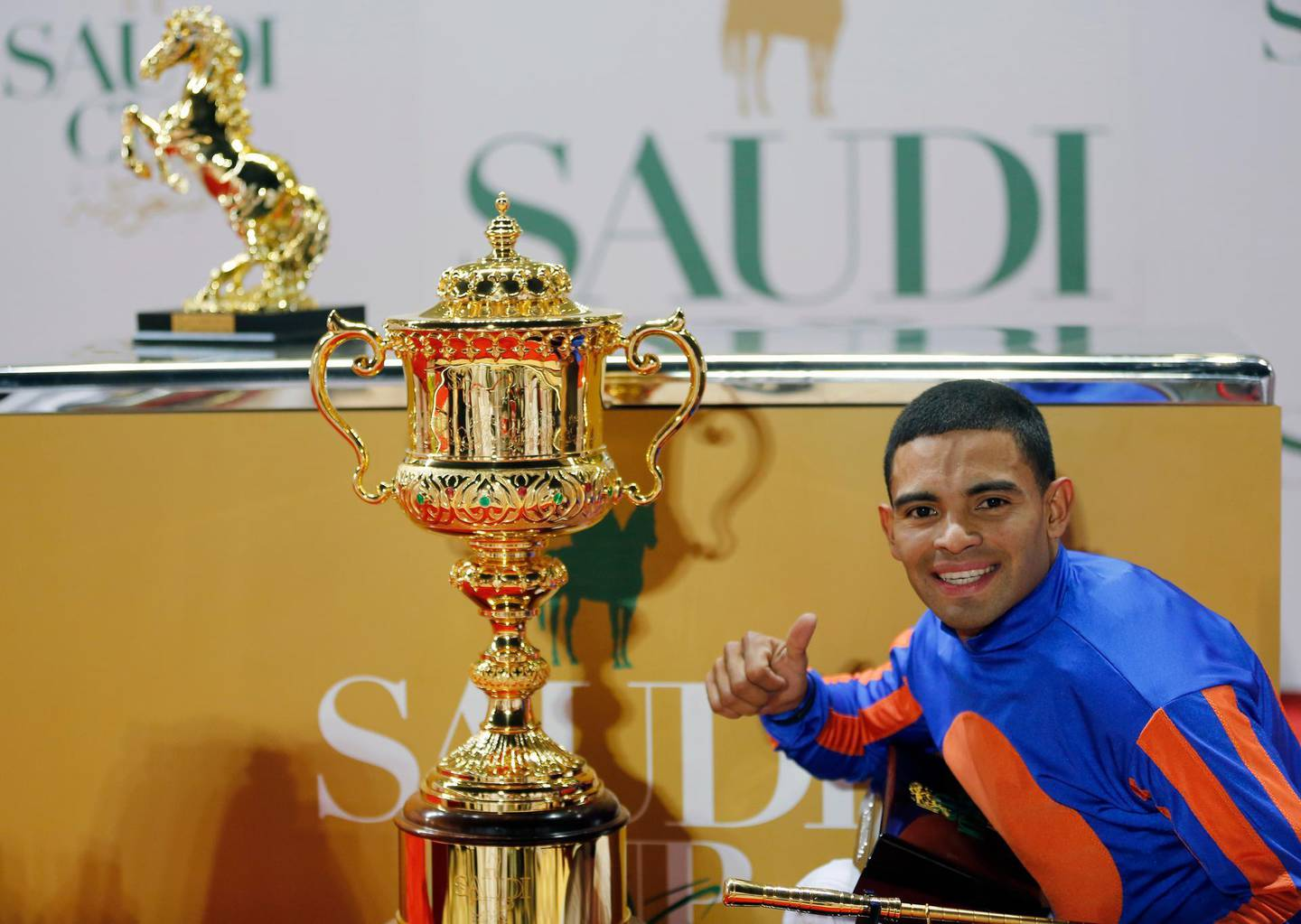 Jockey Luis Saez celebrates with the trophy after winning the final race of the $20 million, the Saudi Cup, at King Abdul Aziz race track in Riyadh, Saudi Arabia, Saturday, Feb. 29, 2020. The race is considered the world's richest horse race which attracted some of the world's best male and female jockeys. (AP Photo/Amr Nabil)