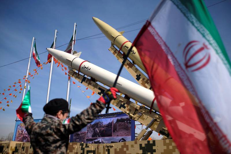 An Iranian young boy wearing an Islamic Revolutionary Guard Corps (IRGC) uniform holds an Iran flag while Iran-made, Dezful medium range ballistic missile (Bottom) and Zolfaghar road-mobile single-stage solid-propelled liquid fueled missile are pictured in the Azadi (Freedom) square during a rally to commemorate the 42nd Victory anniversary of the Islamic Revolution, that held with motorcycles amid the new coronavirus disease (COVID-19) outbreak in Iran, in Tehran on February 10, 2021, on February 10, 2021.  (Photo by Morteza Nikoubazl/NurPhoto via Getty Images)