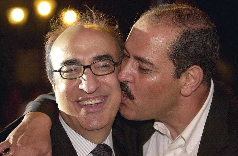 (FILES) In this file photo taken on June 25, 2003, Tunisian singer Lutfi Bushnak kisses late Lebanese musician Elias Rahbani (L) during the Alexandria International Music Festival in the Mediterranean Egyptian port city. Lebanese media reported the death of Elias Rahbani, one of the Arab world's leading pop musicians who is in his early 80s, after a long struggle with illness on January 4, 2021. / AFP / -