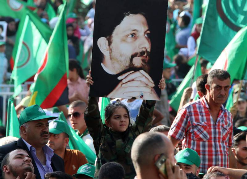 Amal movement supporters hold up pictures of Imam Musa al-Sadr and wave the Shiite movement's green flags during a ceremony held in the town on Baalbeck, east of the capital Beirut on August 31, 2018, to commemorate the disappearance of the former head of the Higher Shiite Council in Lebanon, Imam al-Sadr. - Sadr, the founder of the Amal movement which played a major role in Lebanon's civil war between 1975 and 1990, vanished while on a trip to Libya in 1978. (Photo by STR / AFP)
