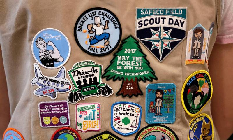 """FILE - In this  June 18, 2018, file photo, patches cover the back of a Girl Scout's vest at a demonstration of some of their activities in Seattle. The Girl Scouts of the United States of America filed a trademark infringement lawsuit on Monday, Nov. 5, against the Boy Scouts of America for dropping the word """"boy"""" from its flagship program in an effort to attract girls. (AP Photo/Elaine Thompson, File)"""