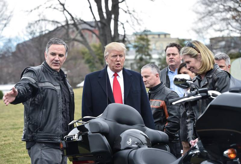 """(FILES) In this file photo taken on February 2, 2017 US President Donald Trump speaks with Harley Davidson CEO Matthew Levatich (L) as he greets Harley Davidson executives and union representatives on the South Lawn of the White House in Washington, DC, prior to a luncheon with them. President Donald Trump on June 26, 2018 renewed his attacks on Harley-Davidson, accusing the motorcycle manufacturer of using the trade war as an """"excuse"""" to move production for the European market out of the United States.""""Early this year Harley-Davidson said they would move much of their plant operations in Kansas City to Thailand. That was long before Tariffs were announced. Hence, they were just using Tariffs/Trade War as an excuse,"""" he said in a tweetstorm about the company. """"When I had Harley-Davidson officials over to the White House, I chided them about tariffs in other countries, like India, being too high ... Harley must know that they won't be able to sell back into U.S. without paying a big tax!"""" / AFP / NICHOLAS KAMM"""