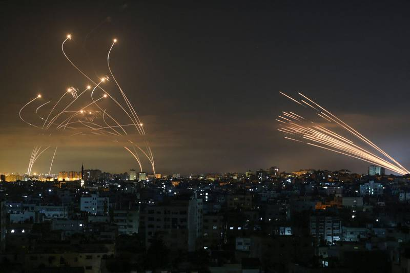 """TOPSHOT - Rockets are seen in the night sky fired towards Israel from Beit Lahia in the northern Gaza Strip on May 14, 2021. Israel bombarded Gaza with artillery and air strikes on Friday, May 14, in response to a new barrage of rocket fire from the Hamas-run enclave, but stopped short of a ground offensive in the conflict that has now claimed more than 100 Palestinian lives. As the violence intensified, Israel said it was carrying out an attack """"in the Gaza Strip"""" although it later clarified there were no boots on the ground.  / AFP / ANAS BABA"""