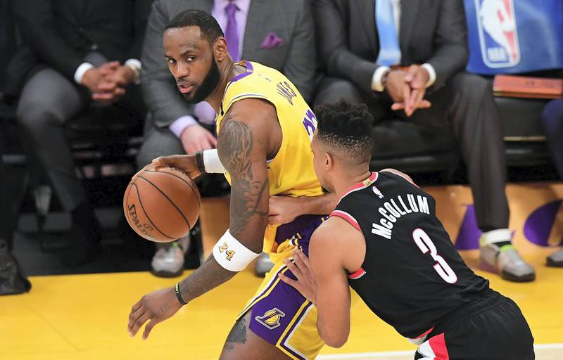 (FILES) In this file photo LeBron James of the Los Angeles Lakers looks to pass under pressure from CJ McCollum of the Portland Trailblazers on January 31, 2020 during their NBA game in Los Angeles. - NBA superstar LeBron James was among the US athletes taking to social media in outrage over the death of a black man in Minnesota after a white policeman kneeled on his neck for several minutes. Four Minneapolis police officers were fired May 26, 2020 as a video showing one of them kneeling on the neck of George Floyd, a handcuffed black man who later died, sparked protests. (Photo by Frederic J. BROWN / AFP)