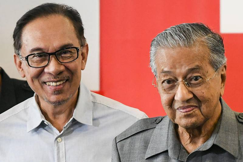 """(FILES) In this file photo taken on June 1, 2018, Malaysia's Prime Minister Mahathir Mohamad (R) and politician Anwar Ibrahim leave after a press conference in Kuala Lumpur. Malaysian politics was in turmoil on February 24, 2020 after leader-in-waiting Anwar Ibrahim denounced a """"betrayal"""" by coalition partners he said were trying to bring down the government, two years after it stormed to victory. / AFP / Mohd RASFAN"""