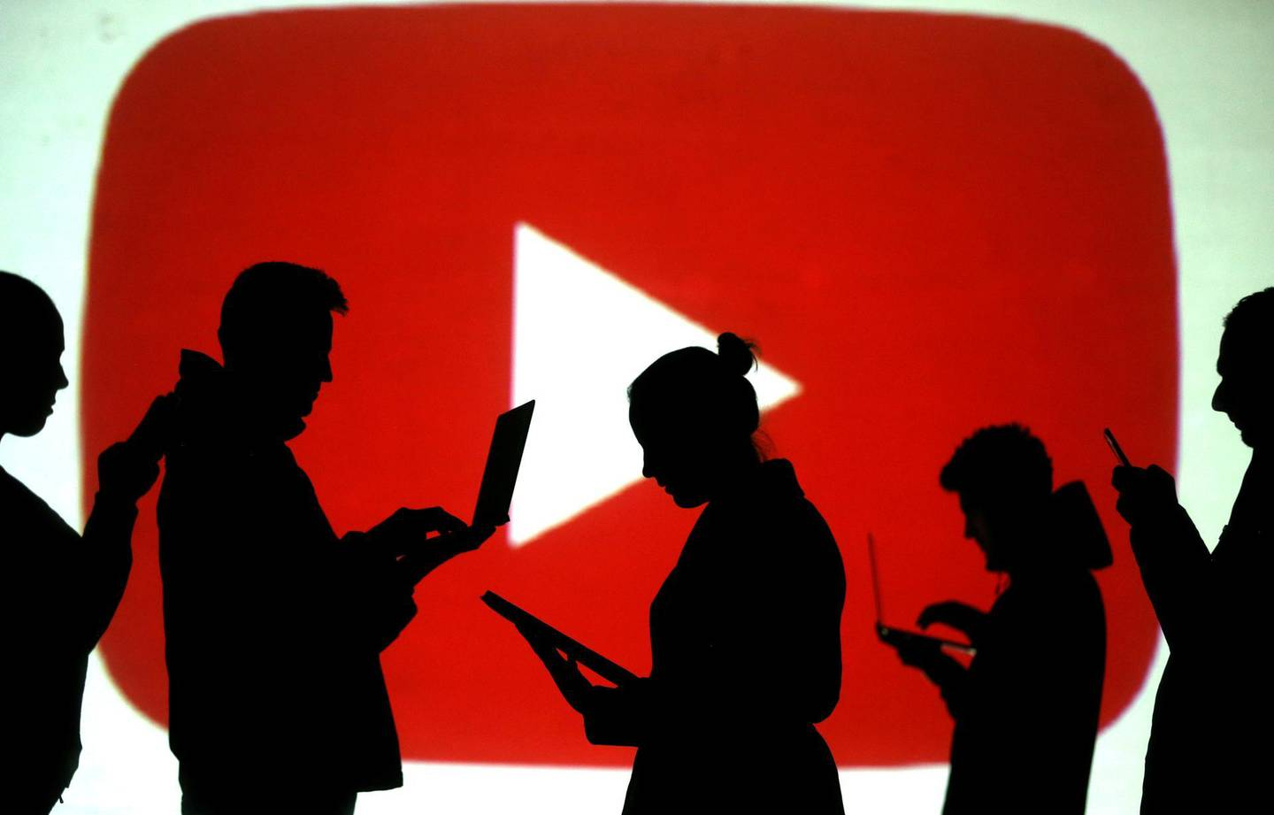 FILE PHOTO: Silhouettes of laptop and mobile device users are seen next to a screen projection of the YouTube logo in this picture illustration taken March 28, 2018.  REUTERS/Dado Ruvic/Illustration/File Photo