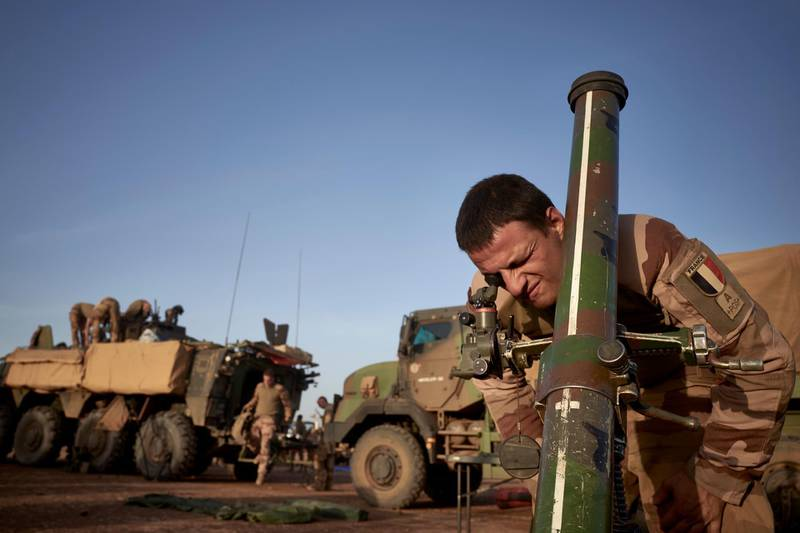 A soldier of the French Army adjusts the coordinates of a mortar ready to be used to defend them at a Temporary Operative Advanced Base (BOAT) during the Bourgou IV operation in Northern Burkina Faso on November 10, 2019. For two weeks in early November, soldiers of the French Army set up a Temporary Operative Advanced Base (BOAT) every evening during the Bourgou IV operation, in the area of the three borders between Mali, Burkina Faso and Niger. There, with their Malian, Burkinabe and Nigerian partners, they combed forests and swamps in search of weapons caches and other jihadist equipment in an area known to harbour them. / AFP / MICHELE CATTANI