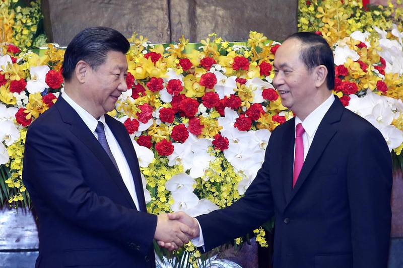 Chinese President Xi Jinping (L) shakes hands with Vietnamese President Tran Dai Quang (R) at Presidential Palace in Hanoi on November 13, 2017. Xi Jinping is on an official visit to Vietnam from November 12-13.  / AFP PHOTO / POOL / LUONG THAI LINH
